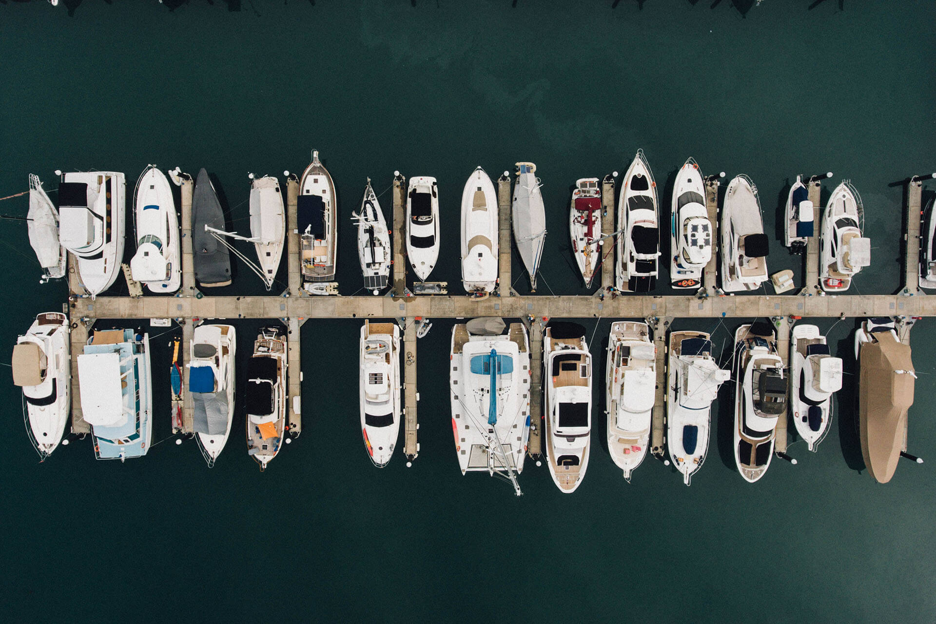 Picture of a dock full of many types of boats on blue-green water. Represents boating insurance