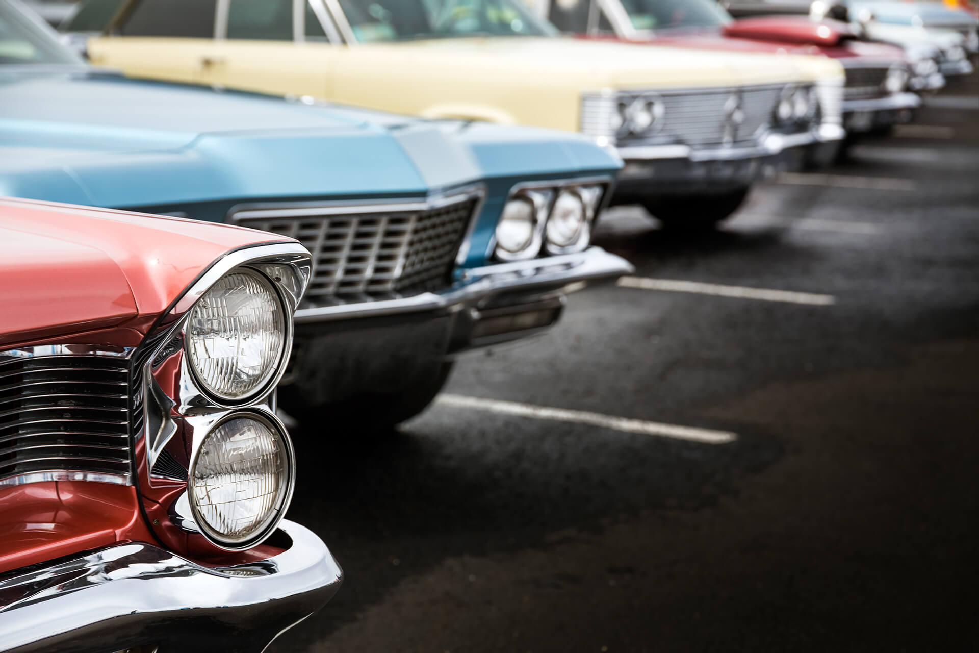 Picture of multiple classic cars lined up in a parking lot. Represents classic car insurance