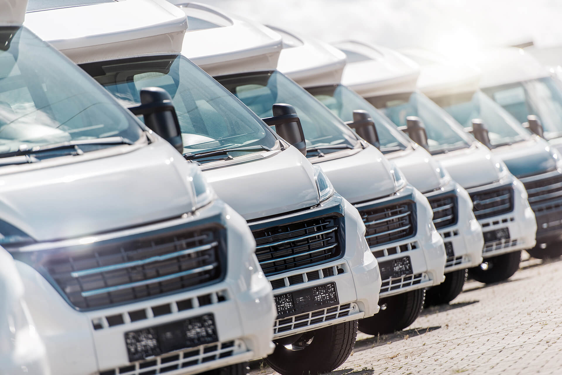 Picture of a fleet of commercial vehicles lined up in the sun. Represents commercial auto insurance