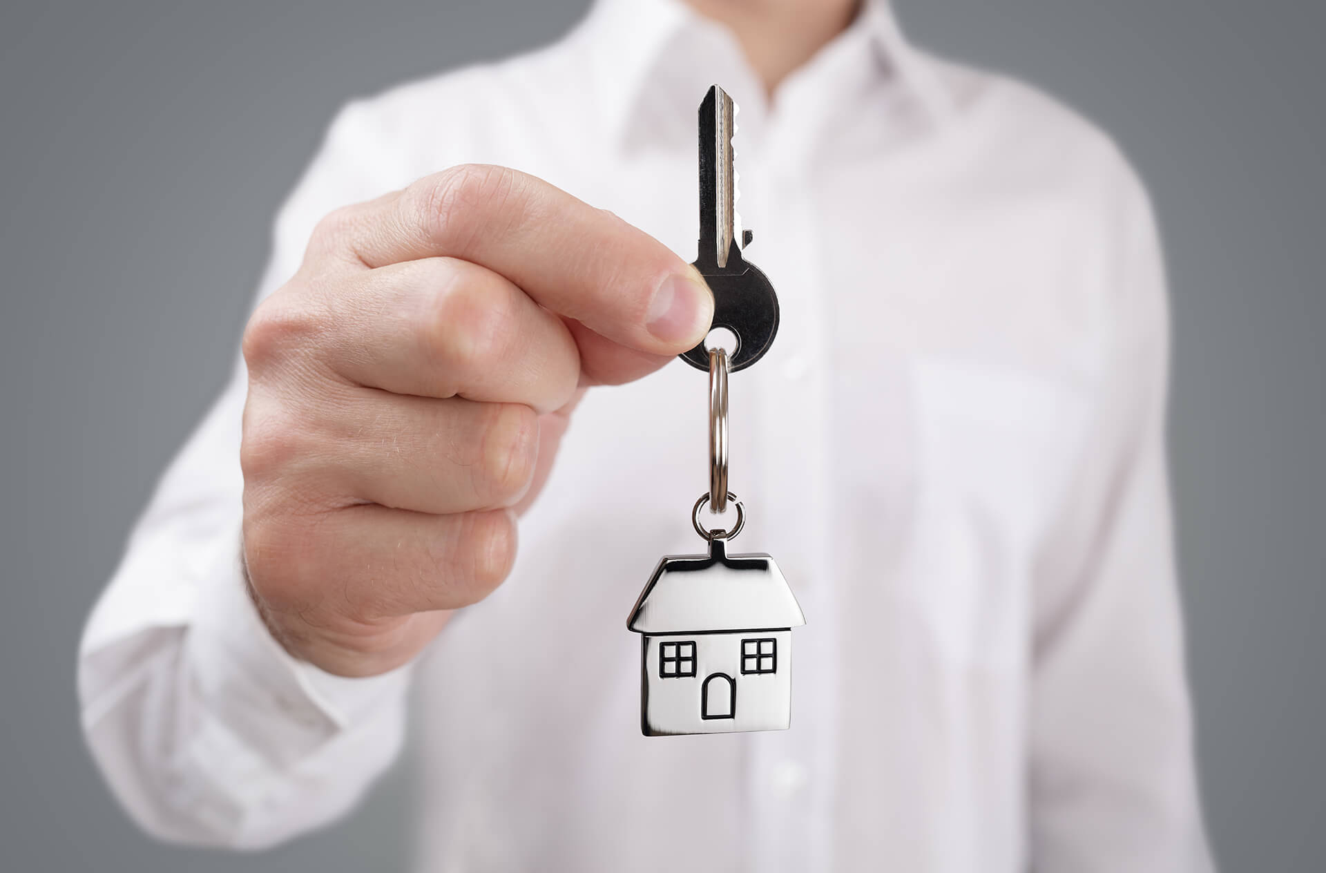 Picture of a landlord handing over the keys to you (the viewer). Represents landlord liability insurance