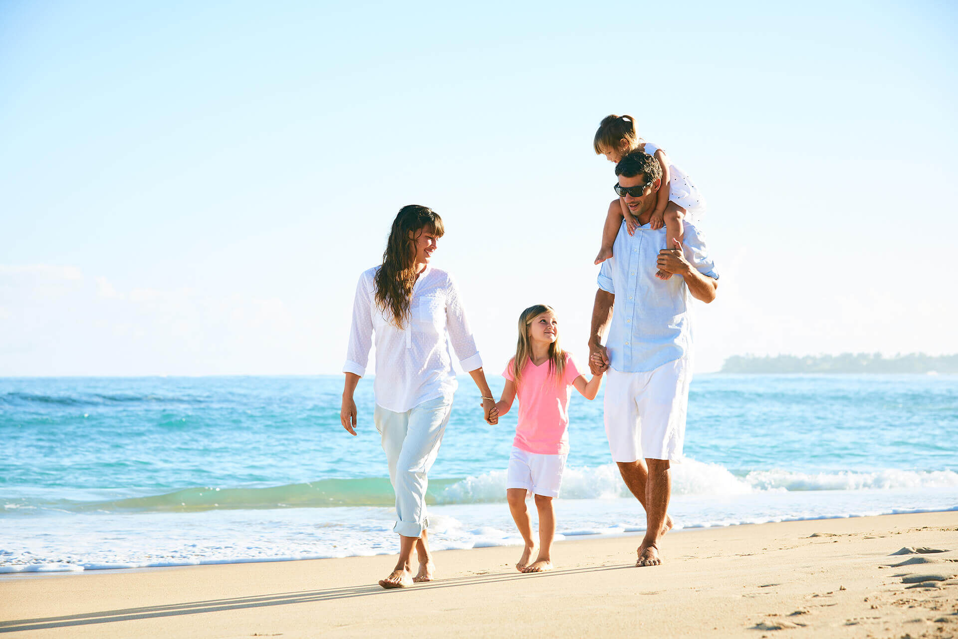 Picture of a family holding hands and walking along the beach. Represents life insurance