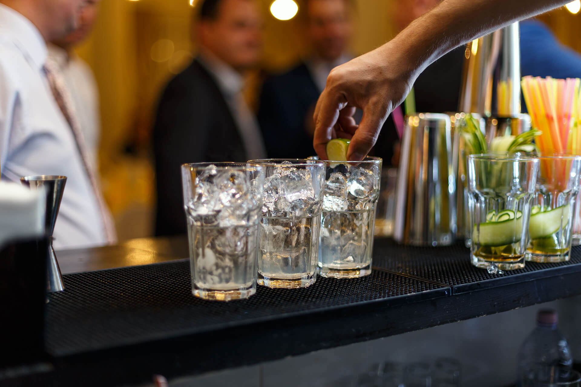 Picture of a bartender squeezing a lime into a glass on the bar. Represents liquor liability insurance