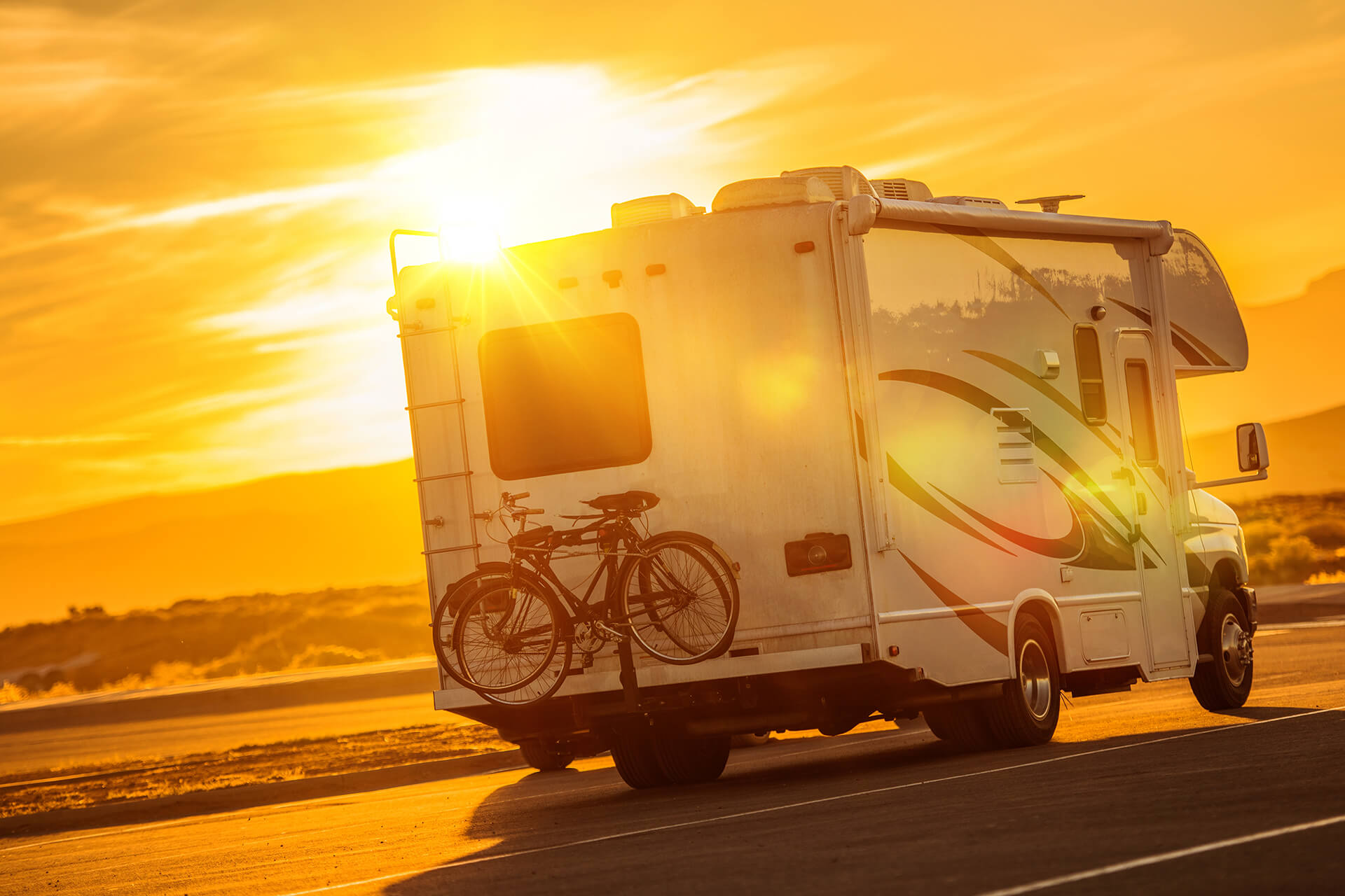 Picture of an RV driving on the highway with the sun behind it. Represents RV insurance