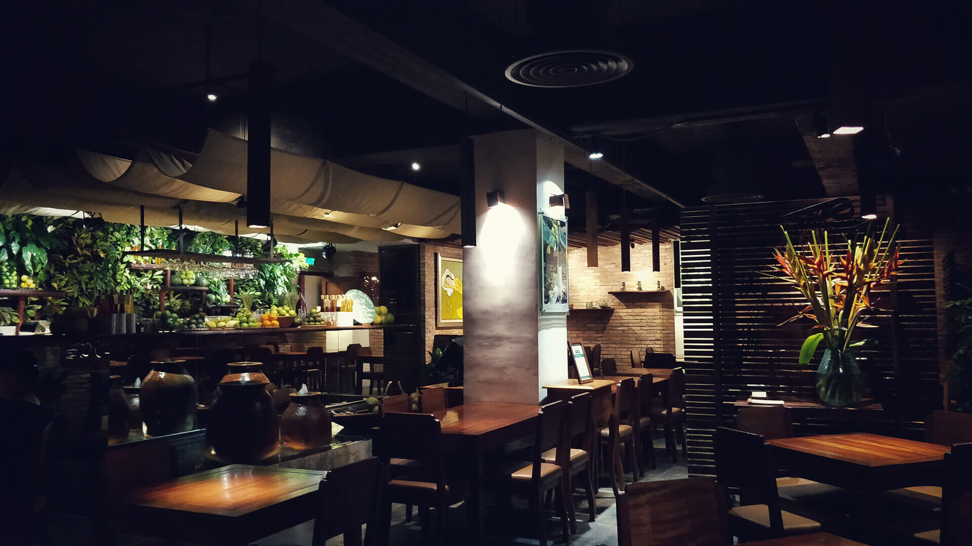 Picture of the inside of a restaurant with mood lightning and plant decor throughout. Represents restaurant insurance